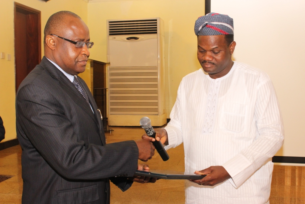 Rep of the MD, NRC Mr. Dottie receiving the plaque presented to the MD, NRC (Engr. Seyi Sijuwade)